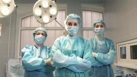Sjuksköterskor korsar deras armar i fungeringsrummet stock video