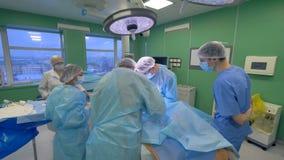 Sjuksköterskor och assistenter döljer kirurgipatienten från sikten lager videofilmer