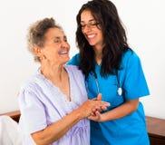 Sjuksköterskor som att bry sig för äldre patienter Arkivbild