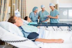 Sjuksköterskor som diskuterar patients kirurgi för stolpe för diagram Arkivfoto