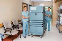Sjuksköterskor som skjuter spårvagnen i sjukhushall Royaltyfri Bild