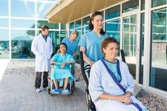 Sjuksköterskor som utanför hjälper patienter på rullstolar Arkivbilder