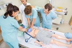 Sjuksköterskor som utför CPR på den falska patienten royaltyfri fotografi