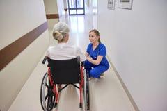 Sjuksköterska med den höga kvinnan i rullstol på sjukhuset Royaltyfri Fotografi
