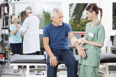Sjuksköterska Putting Crepe Bandage på hög mans hand Arkivbilder