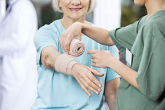 Sjuksköterska Putting Crepe Bandage på patients hand på Rehabmitten Royaltyfri Bild