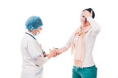 Sjuksköterska som ger läkarbehandlingen till den kvinnliga patienten Arkivfoton