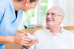 Sjuksköterska som ger receptdroger för hög man Royaltyfri Fotografi