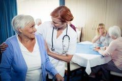 Sjuksköterska som hjälper en pensionär som använder en fotgängare Fotografering för Bildbyråer