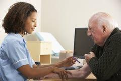 Sjuksköterska som injicerar den höga manliga patienten Royaltyfri Fotografi