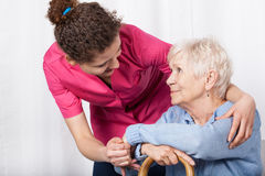 Sjuksköterska som tar omsorg av den höga kvinnan Royaltyfri Bild