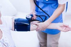 Sjuksköterska som tar omsorg av den sjuka äldre kvinnan Royaltyfri Fotografi