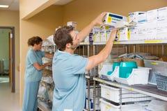 Sjuksköterskor som ordnar materielet i lagringsrum Royaltyfri Foto