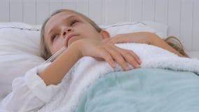 Sjukt barn i säng, dåligt unge med termometern, flicka i sjukhuset, pillermedicin arkivfoton