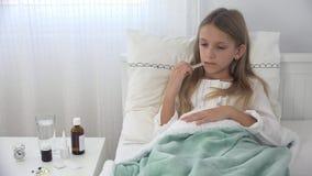 Sjukt barn i säng, dåligt unge med termometern som lider flickan, pillermedicin arkivfilmer