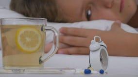 Sjukt barn som dricker te, dåligt unge i säng som lider flickan som är tålmodig i sjukhus fotografering för bildbyråer