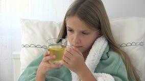 Sjukt barn som dricker te, d?ligt unge i s?ng som lider flickan som ?r t?lmodig i sjukhus arkivfilmer