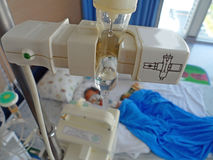 Sjukt barn som ligger i ett sjukhus med dropp Royaltyfria Foton
