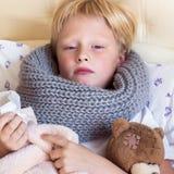 Sjukt barn som ligger i säng arkivbilder