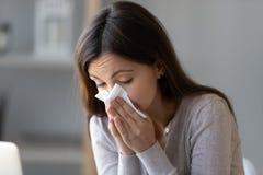Sjukt innehavsilkespapper för ung kvinna och blåsa hennes rinnande näsa arkivbilder