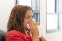 Sjukt sammanträde för ung kvinna på en svart soffa och blåsa hans näsa in i en servett royaltyfria bilder
