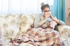 Sjukt sammanträde för ung kvinna på soffan och drickateet Arkivbild