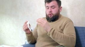 Sjukvård, influensa, hygien och folkbegrepp - sjuk man som hemma blåser näsan till den pappers- servetten arkivfilmer