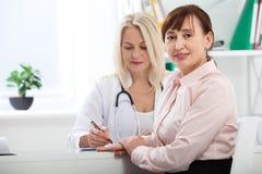 Sjukvård- och läkarundersökningbegrepp - doktor med patienten i sjukhus arkivfoto