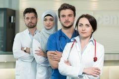 Sjukvård- och medicinbegrepp - den attraktiva manliga doktorn framme av den medicinska gruppen i sjukhusvisning tummar upp Arkivbilder