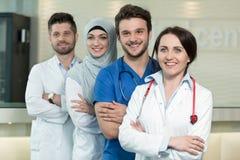 Sjukvård- och medicinbegrepp - den attraktiva manliga doktorn framme av den medicinska gruppen i sjukhusvisning tummar upp Fotografering för Bildbyråer