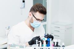 Sjukvård-, yrke-, stomatology- och medicinbegrepp - le den manliga unga tandläkaren över medicinsk kontorsbakgrund Arkivfoto