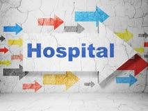 Sjukvårdbegrepp: pil med sjukhuset på grungeväggbakgrund Arkivfoton