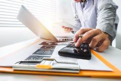 Sjukvårdkostnads- och avgiftbegrepp Handen av den smarta doktorn använde en räknemaskin och en minnestavla för läkarundersökning royaltyfri fotografi