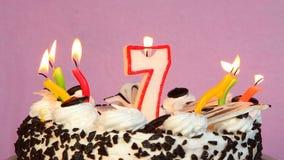 Sjunde beröm för lycklig födelsedag med kakan och stearinljus lager videofilmer