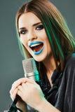 sjunga för flickamikrofon Arkivfoto