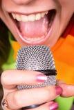 sjunga för flickamikrofon Royaltyfria Bilder