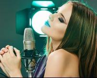 Sjunga för kvinnamikrofon Studio för skönhetmodellsoun Royaltyfri Bild