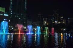 Sjunga kulöra springbrunnar i aftonen i mörkret Kuala Lump royaltyfria foton