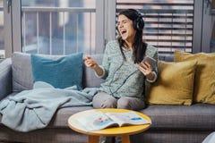 Sjunga sång med sinnesrörelse Övande röst- kapaciteter Förbättra område Gladlynt kvinna som lyssnar till musik med stor hörlurar royaltyfria foton