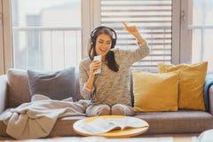 Sjunga sång med sinnesrörelse Övande röst- kapaciteter Förbättra område Gladlynt kvinna som lyssnar till musik med stor hörlurar arkivfoto