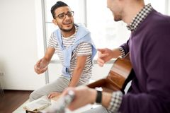 Sjunga till gitarren på det moderna kontoret fotografering för bildbyråer