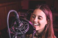 Sjungande flicka som sjunger med en mikrofon royaltyfria bilder
