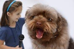 Sjungande karaoke för liten flicka och för stor hund Royaltyfri Bild