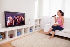 Sjungande karaoke för ung kvinna arkivbilder
