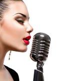 Sjungande kvinna med den Retro mikrofonen Arkivfoton