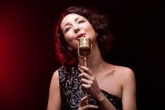 Sjungande lyrisk sång för härlig flickasångare med den retro mikrofonen Royaltyfria Bilder