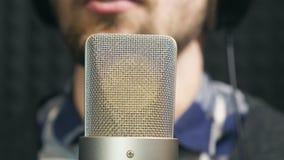 Sjungande sång för manlig oigenkännlig sångare in i mikrofonen på den solida studion Ung man som antecknar ny melodi eller sång arkivfilmer
