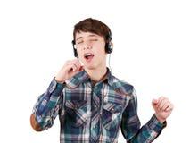 Sjungande tonårig pojke i hörlurar som lyssnar till musik och visar handtecknet som isoleras på vit Fotografering för Bildbyråer