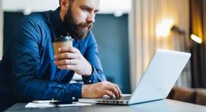 Skäggig affärsman som arbetar på datoren på tabellen som dricker kaffe Mannen analyserar information, data, framkallar affärsplan Arkivfoto