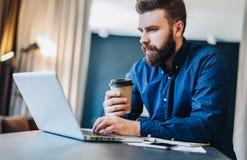 Skäggig affärsman som arbetar på datoren på tabellen som dricker kaffe Mannen analyserar information, data, framkallar affärsplan Arkivfoton